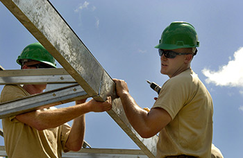 workers with hard hats framing a structure