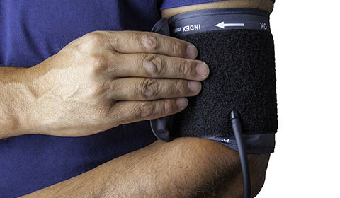 person taking his or her own blood pressure