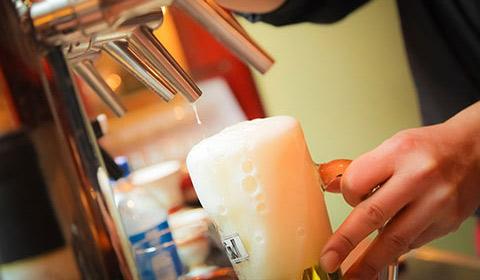 man pouring beer into mug